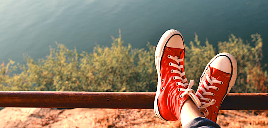 Feet red sneaker a girl in nature and relax time on holiday. selective and soft focus color of vintage tone
