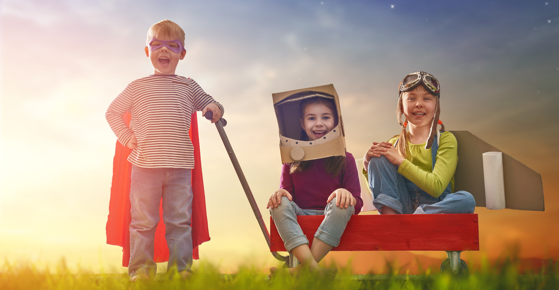 Children in astronaut, pilot and super hero costumes are playing and dreaming. Portrait of funny kids on nature. Family friends games outdoors.