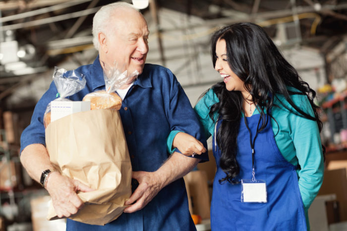 A mid adult female food bank worker walks arm in arm with a a senior male patron and laughs with him as he carries a bag of groceries out the door of the warehouse.